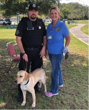 staff volunteer, police officer and service dog.