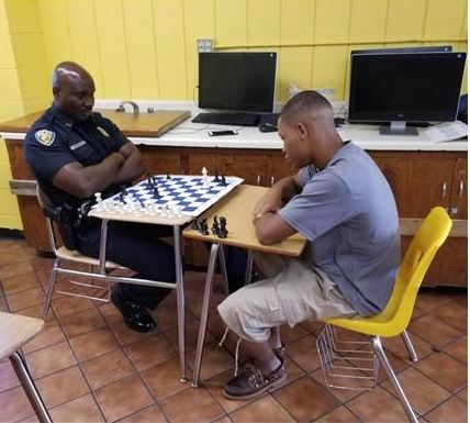 officer playing chess with youth
