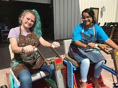 Youth from PACE Center for Girls Clay with their painted personal mobility carts.