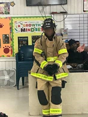 miami firefighter lets youth try on uniform