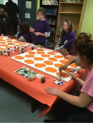 youth painting pumkins